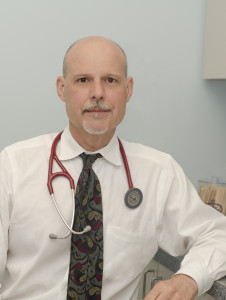 Dr. DeSimone sitting at his desk with a stethascope draped around his neck