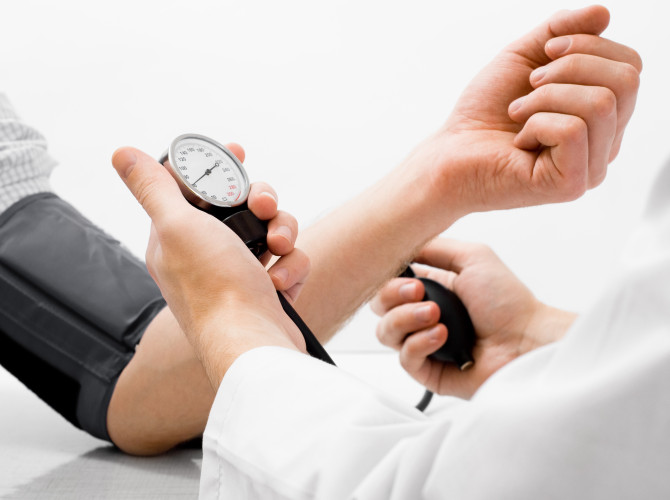 blood pressure measuring by person in white lab coat