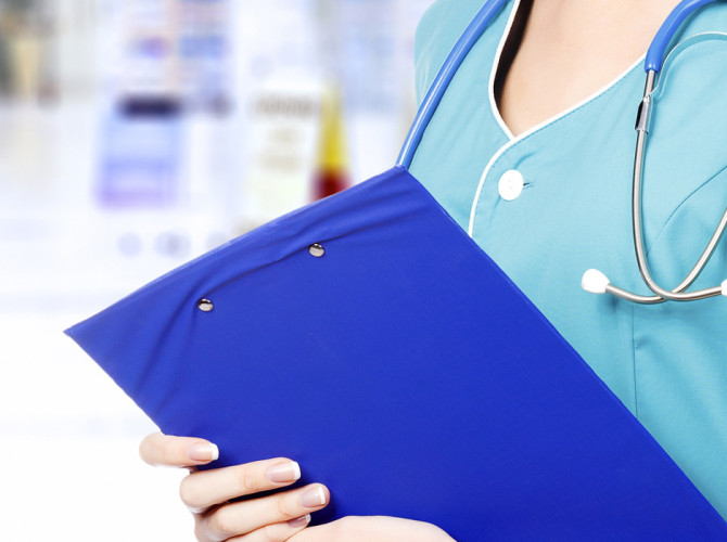 partial view of woman in medical scrubs with stethascope around neck holding a blue clipboard for taking notes